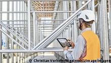Architect with tablet wearing hard hat on construction site model released Symbolfoto property released PUBLICATIONxINxGERxSUIxAUTxHUNxONLY CVF00339