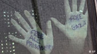 Hands with writing on them pressed against glass