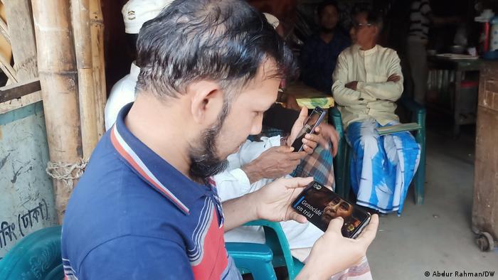রোহিঙ্গা গণহত্যা বিষয়ক একটি প্রতিবেদন দেখছেন এক রোহিঙ্গা শরণার্থী