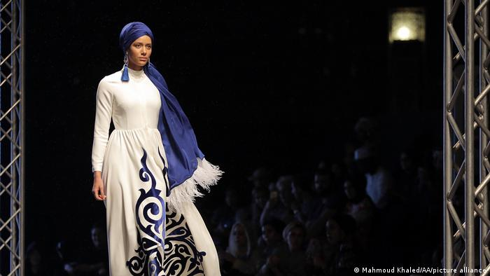 In Dubai, a model presents the creation of Muslima Wear, a white dress with blue motifs, at the 2017 Dubai Modest Fashion Show.