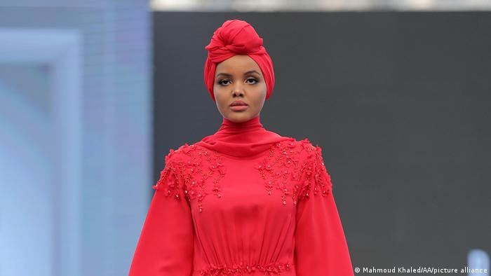 American model Halime Aden in a red robe and a turban-like head covering at Dubai's Modest Fashion Week 2017.