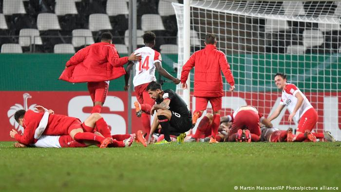 Rot-Weiss Essen's players celebrate as a deflated Karim Demirbay looks down.