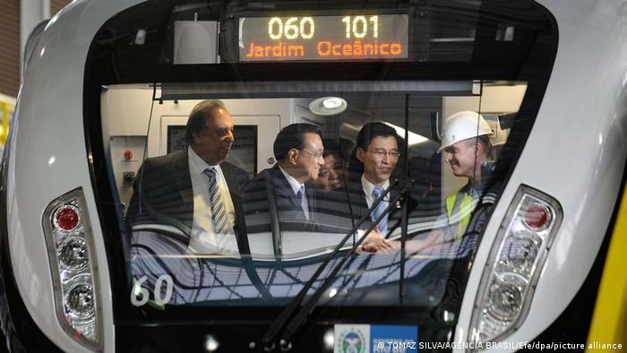 Quatro homens de paletó e gravata na cabine de um metrô