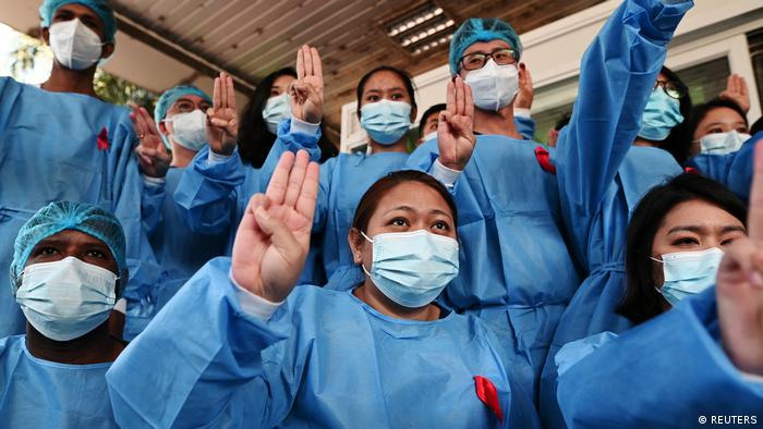 Medical staff in masks protesting with the three-finger salute