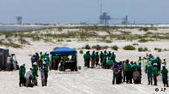 Workers cleaning up oil on a Gulf of Mexico beach