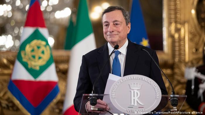Italian economist Mario Draghi in front of flags
