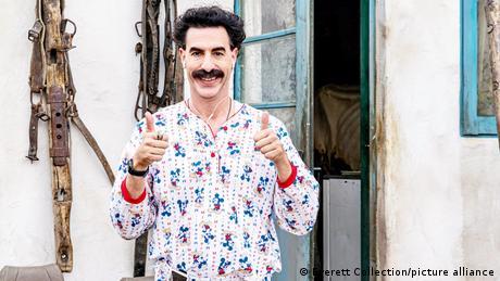 Sacha Baron Cohen als Borat in einem Schlafanzug hält beide Daumen lächelnd nach oben