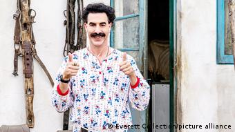 A still of Sacha Baron Cohen as Borat smiling and giving a thumbs up in the film Borat Subsequent Moviefilm