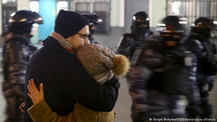 A couple hug as riot police pass