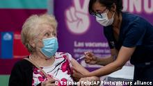 An elderly woman gets a shot of the CoronaVac vaccine for COVID-19 developed by China's biopharmaceutical company Sinovac Biotech, at a clinic in Santiago, Chile, Wednesday, Feb. 3, 2021. Chile is starting its vaccination plan for the general population on Wednesday, starting with seniors over 90 and health workers. (AP Photo/Esteban Felix)