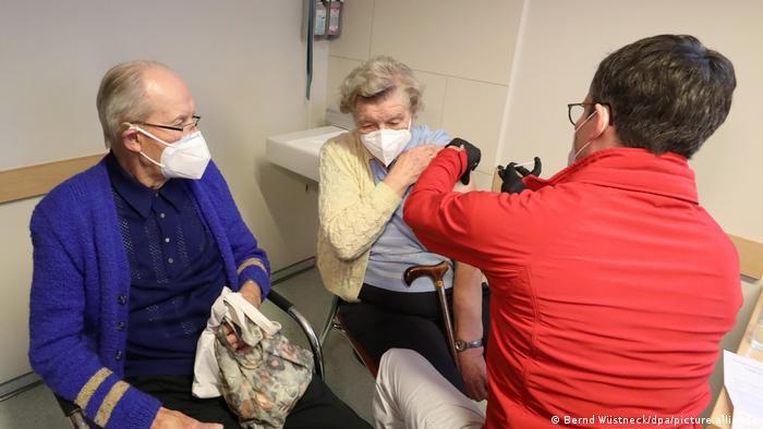 Homem de jaqueta vermelha, máscara e luvas pretas aplica vacina em uma idosa, também de máscara e bengala. Ao lado dela, está um senhor idoso, também de máscara.