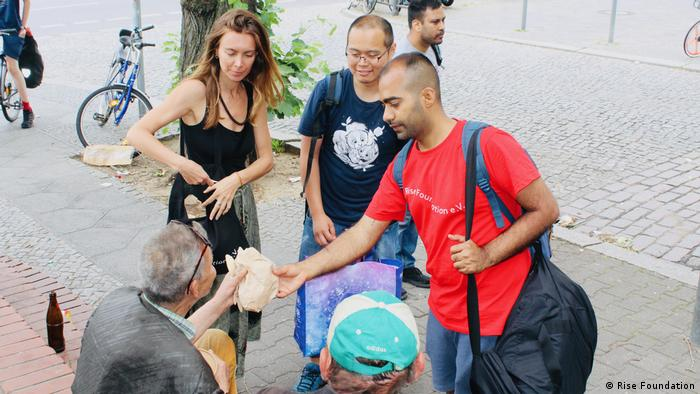 Volunteers from the German charity Rise Foundation hand out supplies to homeless people