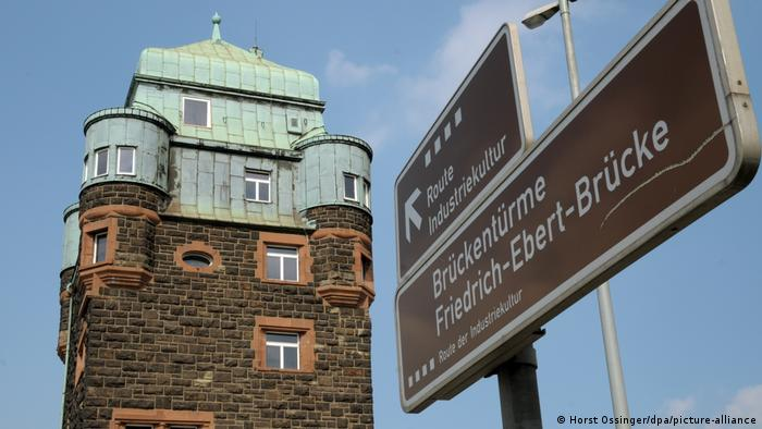A brown sign with 'Friedrich-Ebert Bridge' on it next to a tower