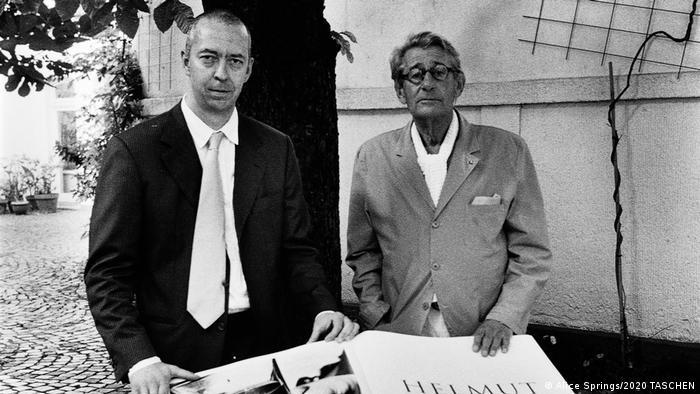 Benedikt Taschen und Helmut Newton präsentieren gemeinsam im Anzug das gigantisch große Buch Nudes auf einem Tisch.