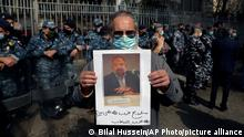 A protester holds up a picture of Lokman Slim after he was found dead in his car