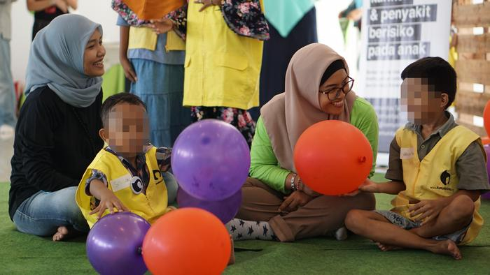 Volunteers from the Indonesian charity Komunitas Taufan play with kids at a hospital
