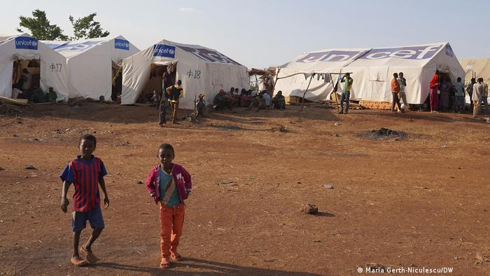 Two children posing for the camera in front of the tents