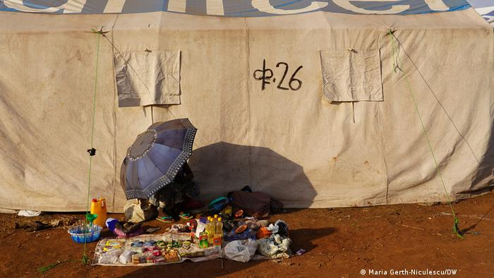 A woman selling small items next to a tent
