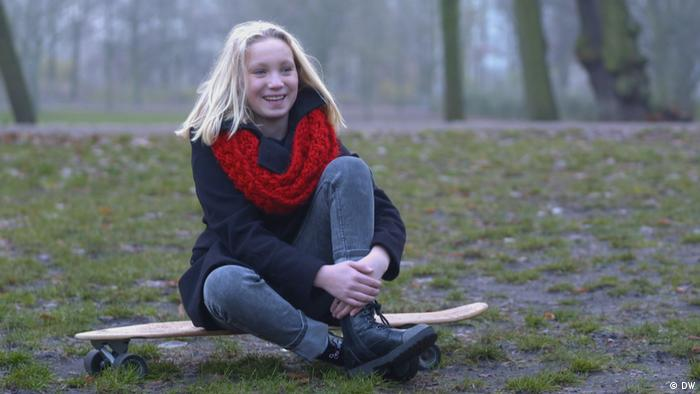 Helena Zengel is sitting in the forest on a skateboard, smiling.