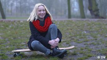 Helena Zengel sitzt auf einem Skateboard und lächelt.