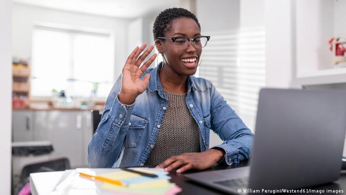 Mulher acena diante do computador