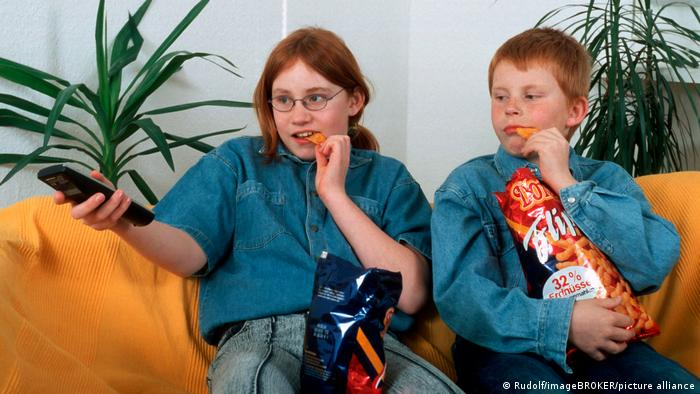 A boy and girl sitting on a sofa watching TV and eating crisps