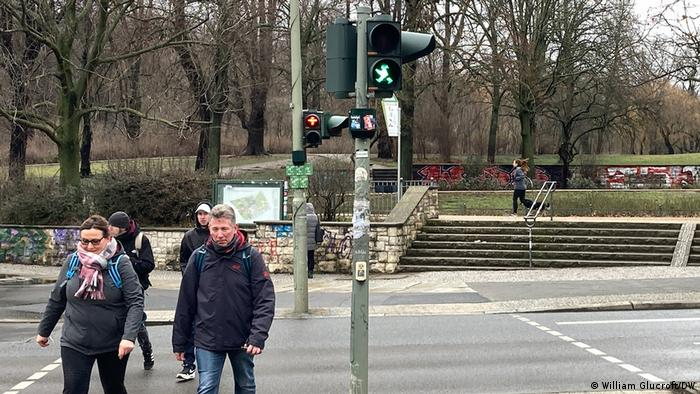 Pedestrians on a crosswalk in Berlin with red and green traffic lights