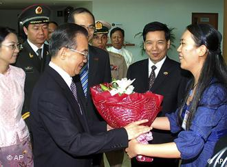 The staff of the Chinese embassy in Yangon presents a bouquet to Chinese PM Wen Jiabao on his arrival on Wednesday