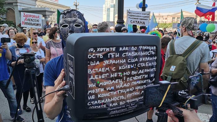 Участник акции держит телевизор, на экран которого нанесены цитаты государственной пропаганды