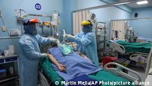 Health workers attend a patient inside the ICU for COVID-19 at Alberto Sabogal Hospital in Callao, Peru, Monday, Jan. 11, 2021. (AP Photo/Martin Mejia)