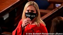 FILE - In this Sunday, Jan. 3, 2021, file photo, Rep. Marjorie Taylor Greene, R-Ga., wears a Trump Won face mask as she arrives on the floor of the House to take her oath of office on opening day of the 117th Congress at the U.S. Capitol in Washington. President Joe Biden's inauguration has sown a mixture of anger, confusion and disappointment among believers in the baseless QAnon conspiracy theory. Greene, who has expressed support for the conspiracy theories, called for Biden's impeachment across her Twitter, Facebook and Telegram accounts as the new president was sworn in, Wednesday, Jan. 20. (Erin Scott/Pool Photo via AP, File)