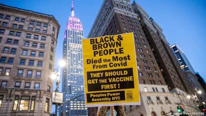 A protester in New York raised a sign to protest racism during vaccination