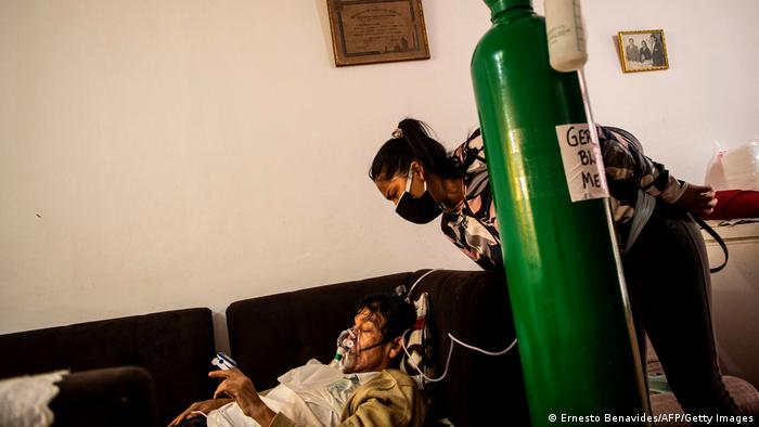 German Blanco's daughter July, 30, checks on her father as he lies on a couch in the living room connected to an oxygen tank at his home in Callao, Peru