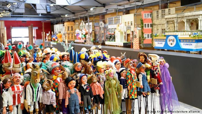 Alle mitwirkenden Puppen vor der Bühnenkulisse: vorne links der Geißbock, das Maskottchen des 1. FC Köln. Auch Blaue und Rote Funken sind bei der Parade dabei.