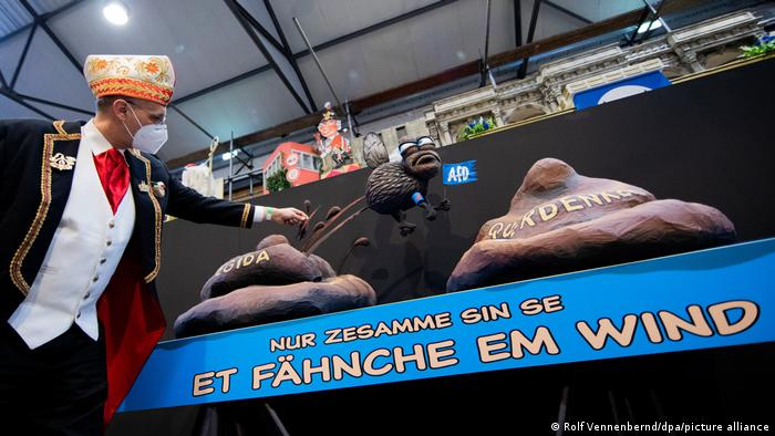 Michael Kramp zeigt den Wagen Et Fähnche em Wind mit zwei Kot-Haufen, die die Aufschrift Pegida und Querdenker tragen. In der Mitte ist eine Fahne der Partei AfD zu sehen.