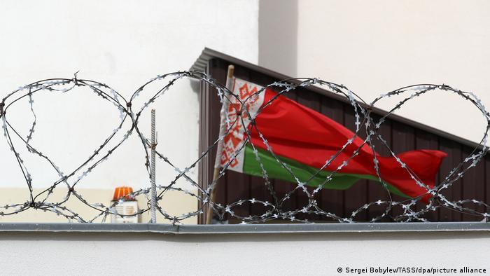 Зелено-красный государственный флаг Беларуси за колючей проволокой