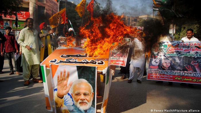 Protesters burn a banner of India's Prime Minister Narendra Modi.