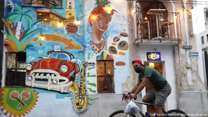 A man on a bicycle passes graffiti in Havana