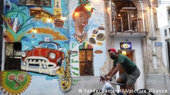 Велосипедист в маске и граффити с автомобилем и саксофоном на улице Гаваны