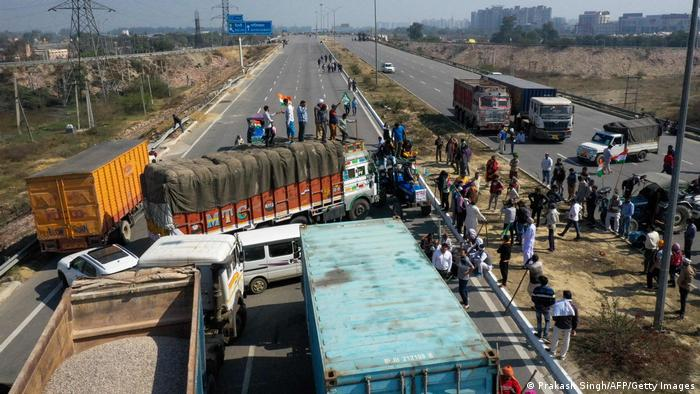Farms block a highway in Haryana state with their trucks