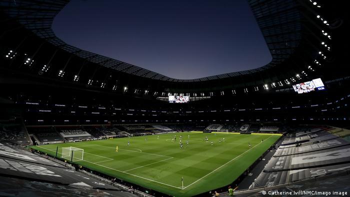 Arquibancadas vazias em estádio durante jogo de futebol