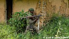A soldier of the FARDC (Armed Forces of the Democratic Republic of the Congo) takes cover during exchanges of fire with members of the ADF (Allied Democratic Forces) in Opira, North Kivu, on January 25, 2018. (Photo by ALAIN WANDIMOYI / AFP)