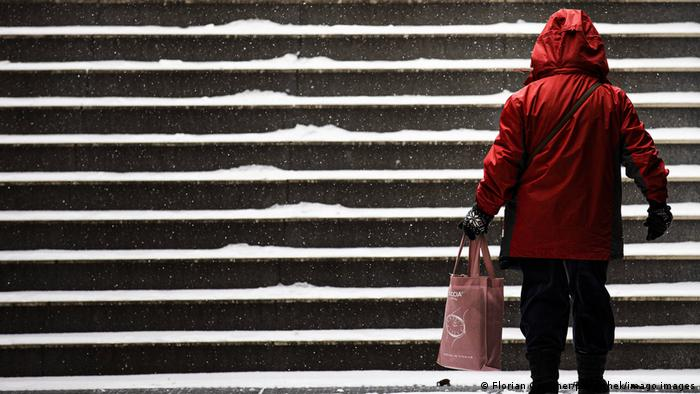 A woman stands by a snow-covered staircase in Berlin