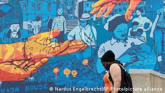 Женщина в маске и граффити в Кейптауне