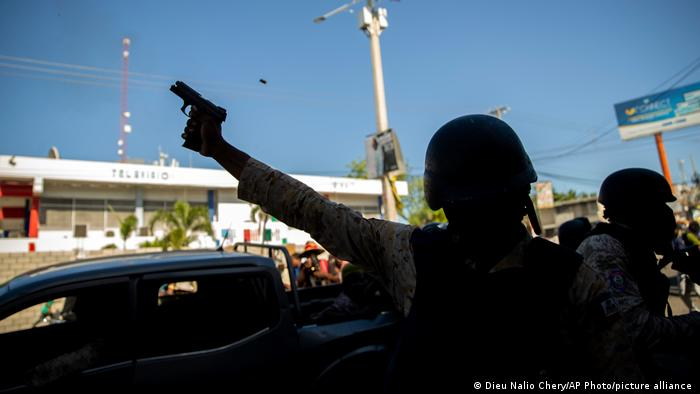 A police officer fires his weapon to disperse demonstrators during a protest to demand the resignation of Haitian President Jovenel Moise in Port-au-Prince, Haiti, Sunday, Feb. 7, 2021.