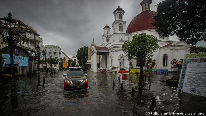 Car driving through a flooded street in Semarang, Indonesia