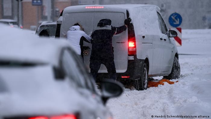 Die Leute schieben den Truck in den Schnee