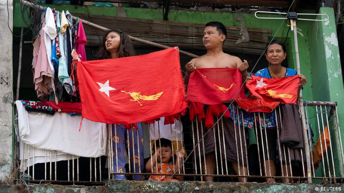 Three people holding NLD party flags on a balcony in Yangon, with young child on the ground holding onto the railings