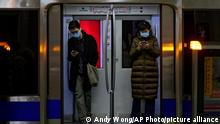 """*** Dieses Bild ist fertig zugeschnitten als Social Media Snack (für Facebook, Twitter, Instagram) im Tableau zu finden: Fach """"Images"""" —> Weltspiegel/Bilder des Tages *** Commuters wearing face masks to help curb the spread of the coronavirus browse their smartphones inside a subway train in Beijing, Monday, Feb. 8, 2021. China appears to have stamped out its latest coronavirus outbreaks centered on the northeast, reporting no new cases of local infection in its latest daily report. (AP Photo/Andy Wong)"""
