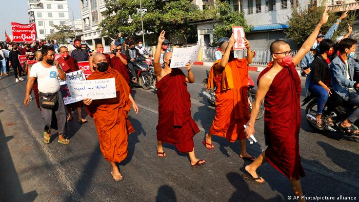 Buddhist monks marching in protest along a street in Mandaly, Myanmar